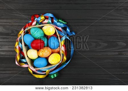 Easter Eggs In A Basket On A Black Wooden Background, Copy Spase
