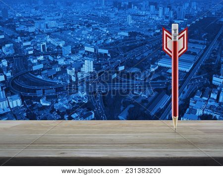 Red Pencil In The Shape Of A Dart On Wooden Table Over Modern Office City Tower Background, Business