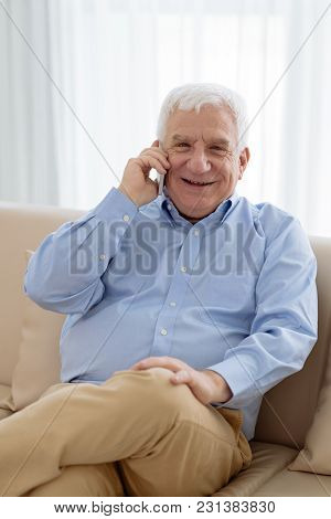 Portrait Of Smiling Aged Businessman Calling On Smartphone