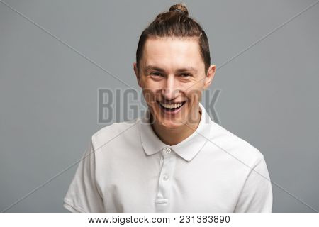 Image of laughing young man standing isolated over grey wall background. Looking camera.