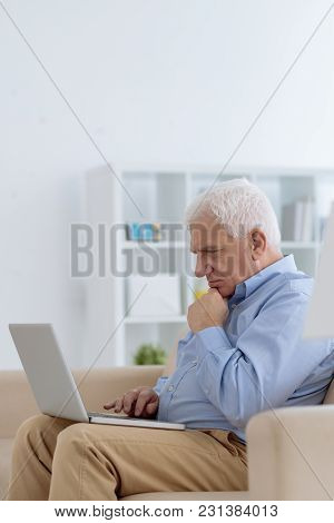 Concentrated Aged Man Reading Information On Laptop Screen