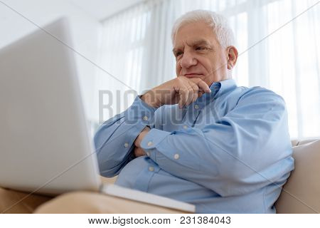 Elderly Man Sitting On Comfy Sofa And Watching Something On Laptop