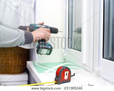 Measuring Ruler Tape In The Foreground And A Man Drilling In The Blurred Background
