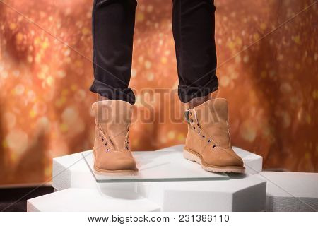 Person With Trendy Brown Shoes And Dark Skinny Jeans On  Pieces Of Styrofoam.