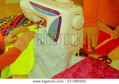 Couturier Sews A Dress In The Studio. Fashion Designer Making A Pattern On A Red Piece Of Tissue. Se