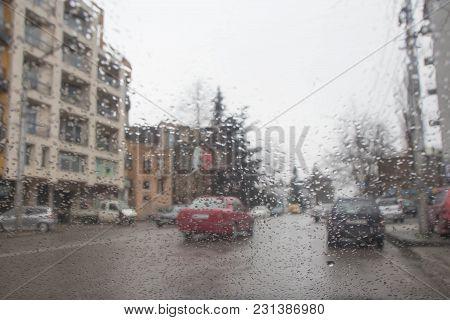 Drops Of Rain On Glass Background. Rain Drops On Window, Rainy Weather, Blurry Car Silhouette
