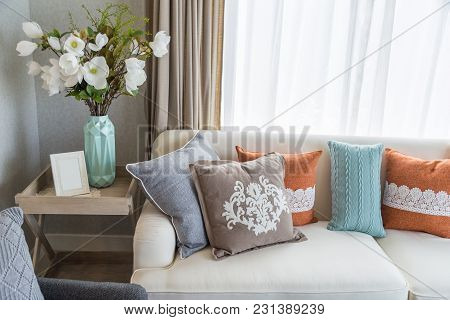 An Interior Picture Of Livingroom With Colorful Pillows On Beige Sofa And Flowers On A Ceramic Vase