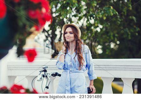 Beautiful Young Woman Standing Next To Her Bike Outdoors