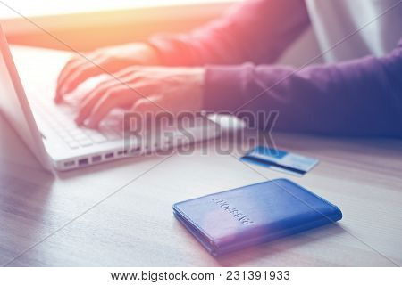 Man With Laptop, Passport And Credit Card Making Online Shopping, Intentional Sun Glare And Lens Fla