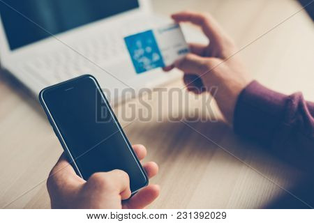 Credit Card And Smartphone In Hands. Laptop On The Table