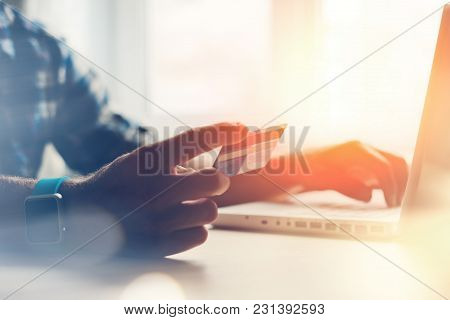 Man Holding Credit Card And Using Laptop. Online Payment, Intentional Sun Glare And Lens Flares