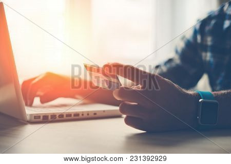 Man Holding Credit Card And Using Laptop. Online Shopping, Intentional Sun Glare And Lens Flares