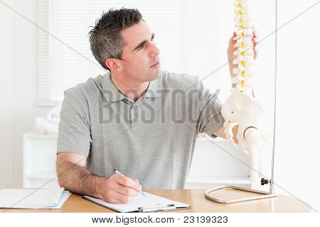 Doctor Sitting At A Table Counting Vertabras