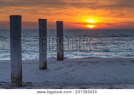 Wooden Piles On An Empty Beach And A Beautiful Sunset Sky Over The Sea, Petten, Holland,north Sea