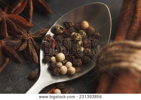 Various Kinds Of Pepper In Metal Spoon, Star Anise And Cinnamon On Dark Old Table Or Background. Dar