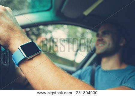 Cheerful Man In The Car With Smart Watch On The Arm