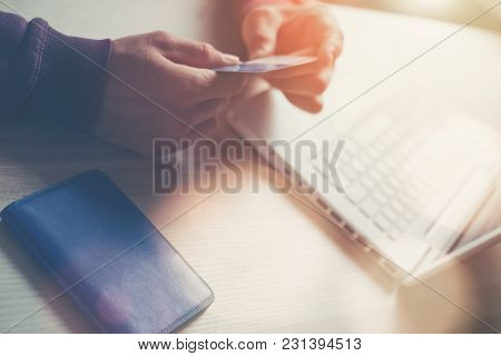 Man Holding Bank Card. Laptop And Wallet On The Table. Online Shopping, Intentional Sun Glare And Le