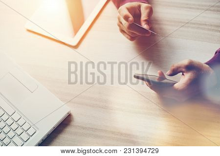 Credit Card And Smartphone In Hands. Laptop And Tablet On The Table. Web Shopping., Intentional Sun