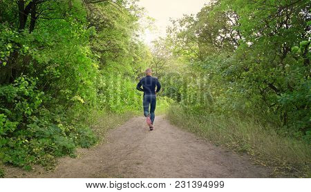 Slim  Athletic Jogger In A Black Sports Leggins, Shirt And Sneakers Runs On The  Green Spring Forest