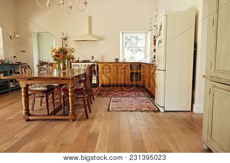 Interior Of A Country Style Kitchen In A Bright Residental Home With A Dining Table, Chairs And Appl