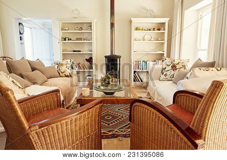 Interior Of A Country Style Living Room With A Sofa, Chairs And Fireplace In A Bright Residential Ho