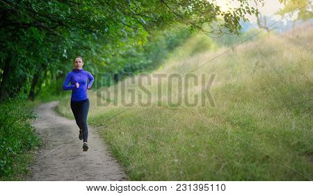 Athleic Jogger In A Black Sports Leggins And And Blue Jacket  Fast Runs Along The Path  On The  Beau