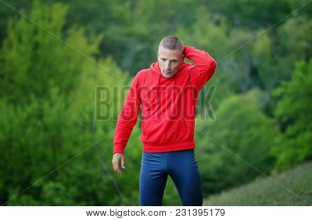 Runner In Red Jacket With A Hood And Black Sport Leggins Rest After Jogging On A Colorful Green Fore