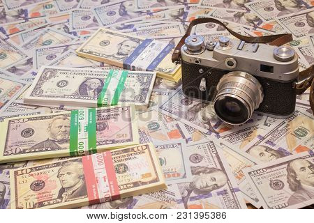A Retro Camera On The Background Of Money. Hobby And Business In One Photo