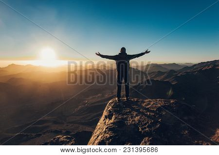 Man Stands Facing The Rising Sun And Meditates On Mount Sinai In Egypt.