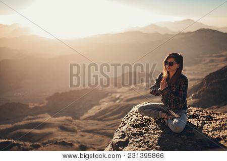 Woman Sits In A Pose Of Yoga On Edge Of Cliff On Mount Sinai And Meditates Against Background Of Bea