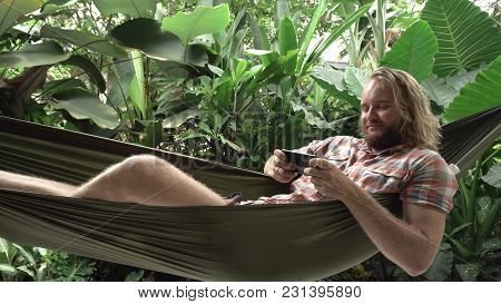 Young Man Playing Game On Smartphone While Sitting On Hammock, Exotic Background