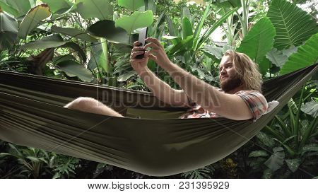 Man Taking Selfie On His Smartphone While Sitting On Hammock, Exotic Background