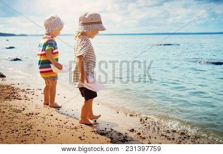Babygirl And Babyboy Standing On The Beach In Summer Hats And Holding Paper Ships
