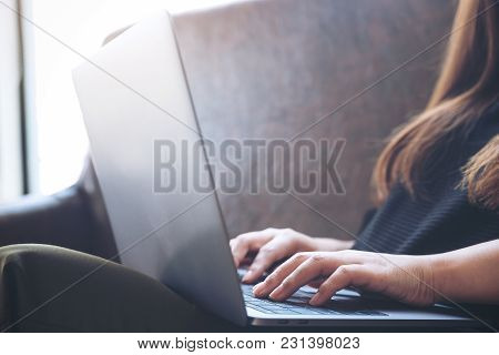 Closeup Image Of A Woman Working And Typing On Laptop Keyboard While Sitting On Sofa