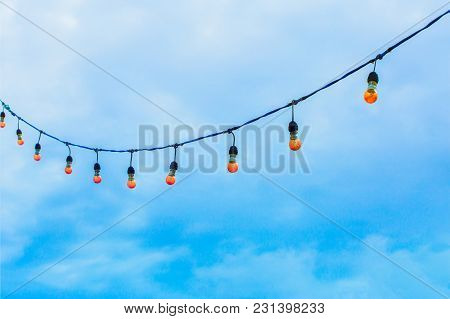 Row Of Electric Light Bulbs Hanging On The Wires Againt Beautiful Blue Sky