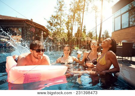 Company Of Young People Spend Weekend In Pool. Guys And Girls Are Resting At Summer Time. Summer Vac