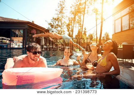 Multiethnic Company Of People In Swimming Pool. Company Of Young People Spend Weekend In Pool. Guys