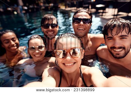 Summer Vacation Friends Together At Swimming Pool Party. Swimming Pool Party. Company Of Young Peopl