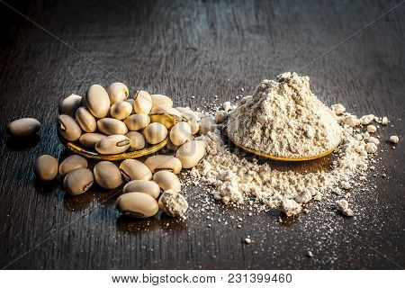 Close Up Of Ayurvedic Herb Kuanch,cowhage,mucuna Pruriens With Powder On A Brown Wooden Surface In D