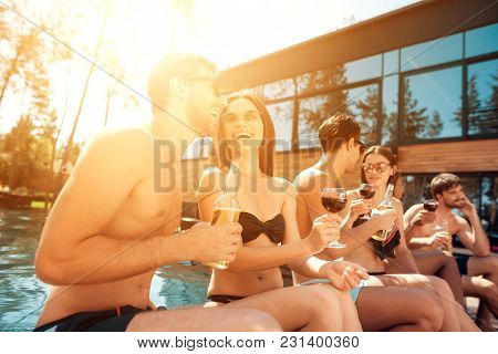 Summer Vacation Friends At Swimming Pool Party. Company Of Young People Spend Weekend In Pool. Holid
