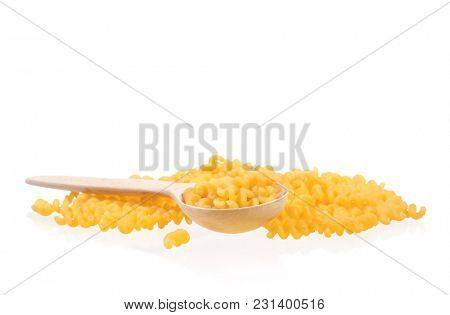 Wooden spoon with dry yellow pasta isolated on white background. Uncooked Italian raw pasta.