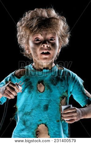 Portrait of funny little electrician over black background