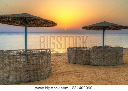 Parasols on the beach of Red Sea in Hurghada at sunrise, Egypt