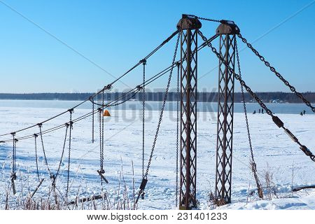 Destroyed Suspension  Ancient  Bridge. The Remains Of An Hanging Axle. Winter Conceptual Story About