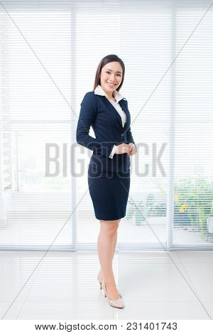 Full Body Shot Of Confident Asian Businesswoman Standing In Office