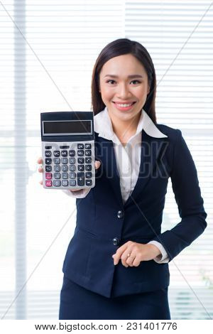 Smiling Businesswoman Portrait In Office Standing And Holding Calculator