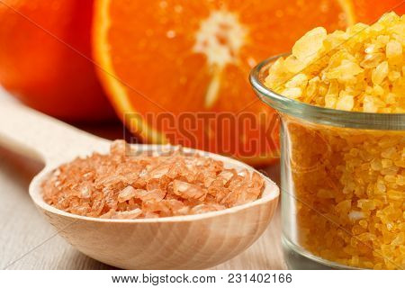 Cut Orange, Wooden Spoon With Brown Sea Salt And Glass Bowl With Yellow Sea Salt On Wooden Desk. Spa