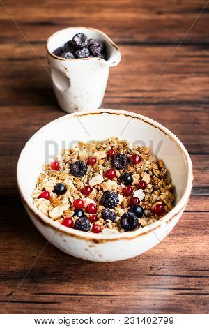 Breakfast Bowl Of Homemade Granola Or Muesli With Toasted Oat Flakes, Peanuts, Black Raspberry, Red