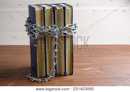 Forbidden Book Are Entangled In A Metal Chain, On A Wooden