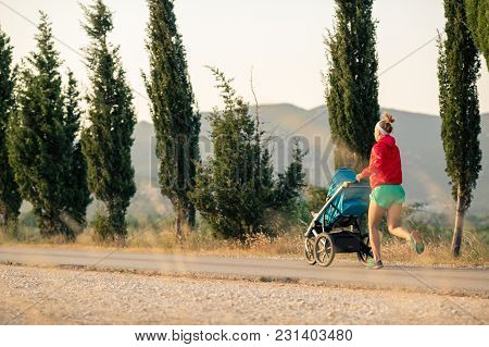 Running mother with child in baby stroller enjoying sunset and mountains landscape. Jogging or power walking supermom, active family at sunset. Beautiful inspirational mountains landscape. poster